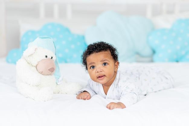 Afro-amerikaanse kleine baby in een wieg in de slaapkamer liggend op haar buik met een knuffel