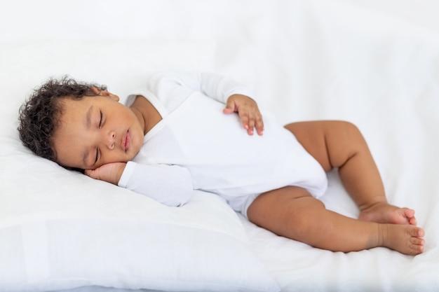 Afro-amerikaanse kleine baby slaapt thuis op een wit bed met haar hand onder haar wang gevouwen