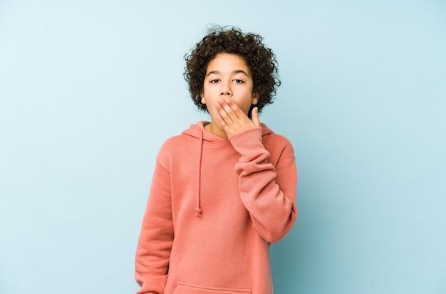 Afro-amerikaanse kleine jongen geeuwt met een moe gebaar dat mond behandelt met hand.