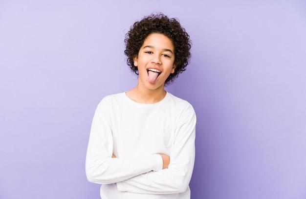 Afro-amerikaanse kleine jongen geïsoleerd grappig en vriendelijk tong uitsteekt.