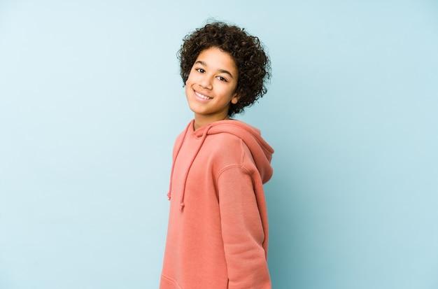 Afro-amerikaanse kleine jongen geïsoleerd kijkt opzij glimlachend, vrolijk en aangenaam.