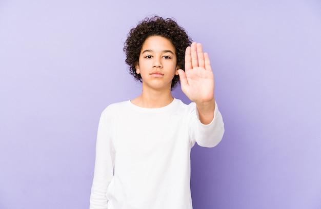 Afro-amerikaanse kleine jongen geïsoleerd staande met uitgestrekte hand weergegeven: stopbord, waardoor u.