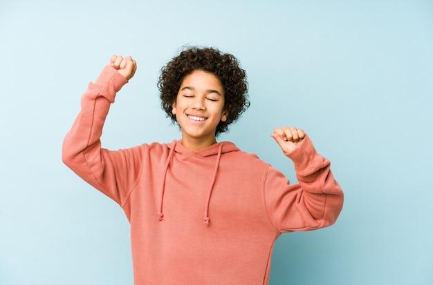 Afro-amerikaanse kleine jongen geïsoleerd viert een speciale dag, springt en heft de armen op met energie.