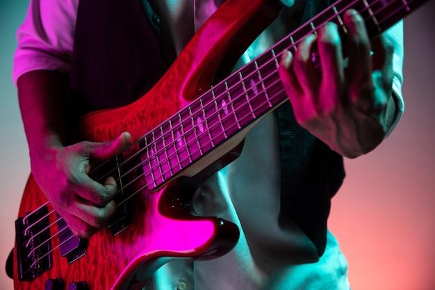 Afro-amerikaanse knappe jazzmuzikant basgitaar spelen in de studio op een neon achtergrond. muziek concept. jonge vrolijke aantrekkelijke kerel improviseren. retro portret van de close-up.