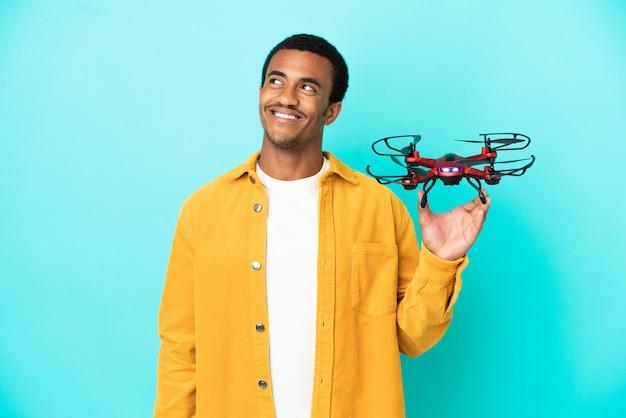 Afro-amerikaanse knappe man die een drone vasthoudt over een geïsoleerde blauwe achtergrond en een idee denkt terwijl hij omhoog kijkt