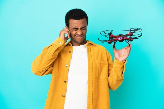 Afro-amerikaanse knappe man die een drone vasthoudt over geïsoleerde blauwe achtergrond, gefrustreerd en oren bedekt