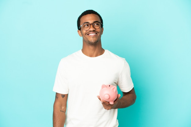 Afro-amerikaanse knappe man die een spaarpot vasthoudt over een geïsoleerde blauwe achtergrond en een idee denkt terwijl hij omhoog kijkt