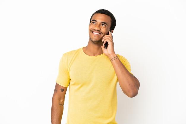 Afro-amerikaanse knappe man die mobiele telefoon gebruikt over een geïsoleerde witte achtergrond en een idee denkt terwijl hij omhoog kijkt