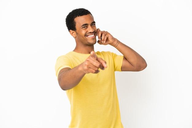 Afro-amerikaanse knappe man met behulp van mobiele telefoon over geïsoleerde witte achtergrond wijzend naar voren met gelukkige uitdrukking