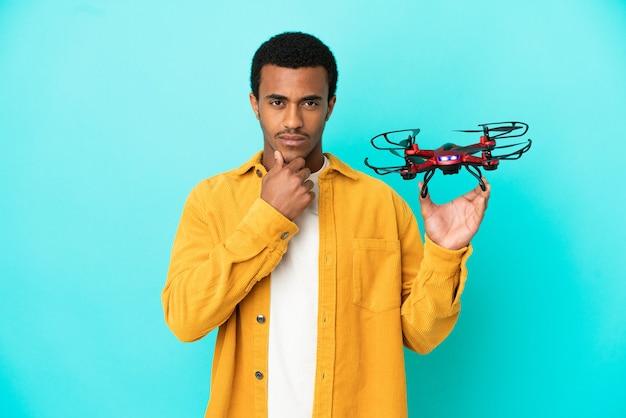 Afro-amerikaanse knappe man met een drone over geïsoleerde blauwe achtergrond denken background
