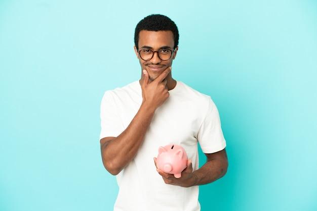 Afro-amerikaanse knappe man met een spaarpot over geïsoleerde blauwe achtergrond denken background