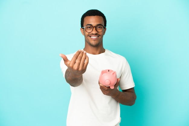 Afro-amerikaanse knappe man met een spaarpot over geïsoleerde blauwe achtergrond die uitnodigt om met de hand te komen. blij dat je gekomen bent