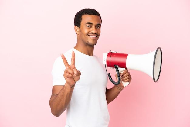 Afro-amerikaanse knappe man op geïsoleerde roze achtergrond die een megafoon vasthoudt en glimlacht en een overwinningsteken toont