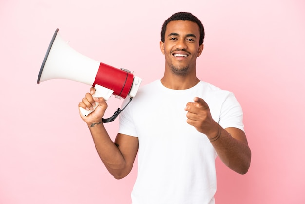 Afro-amerikaanse knappe man op geïsoleerde roze achtergrond die een megafoon vasthoudt en glimlacht terwijl hij naar voren wijst