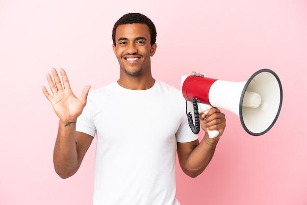 Afro-amerikaanse knappe man op geïsoleerde roze achtergrond die een megafoon vasthoudt en met de hand salueert met een gelukkige uitdrukking