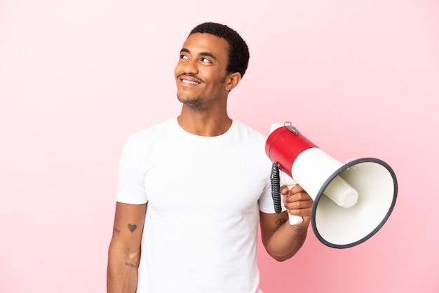 Afro-amerikaanse knappe man op geïsoleerde roze achtergrond die een megafoon vasthoudt en omhoog kijkt terwijl hij glimlacht