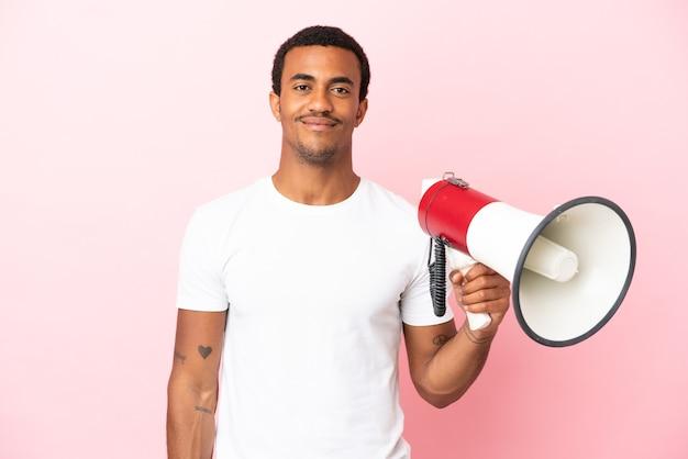 Afro-amerikaanse knappe man op geïsoleerde roze achtergrond die een megafoon vasthoudt en veel lacht