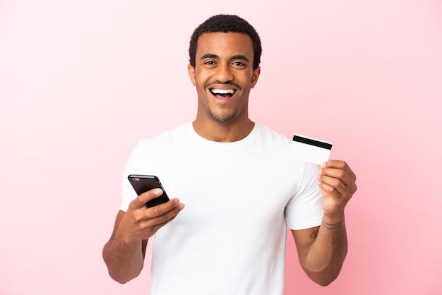 Afro-amerikaanse knappe man op geïsoleerde roze achtergrond die met de mobiel koopt en een creditcard vasthoudt met een verbaasde uitdrukking