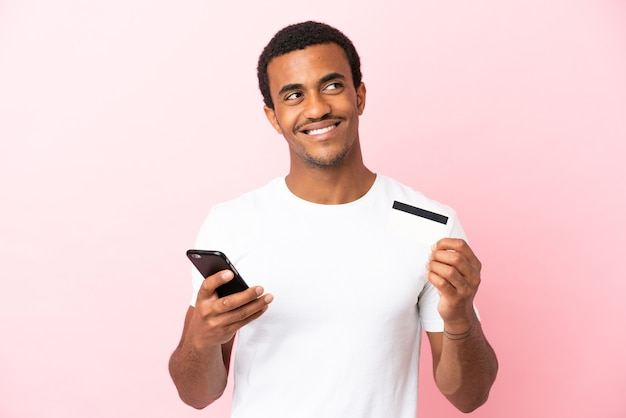 Afro-amerikaanse knappe man op geïsoleerde roze achtergrond kopen met de mobiel met een creditcard terwijl hij denkt