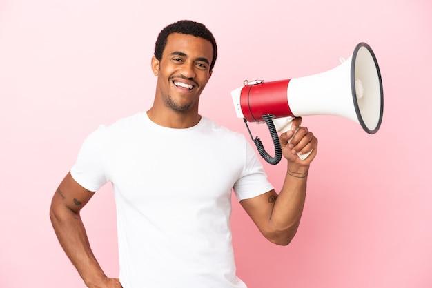 Afro-amerikaanse knappe man op geïsoleerde roze achtergrond met een megafoon en glimlachend