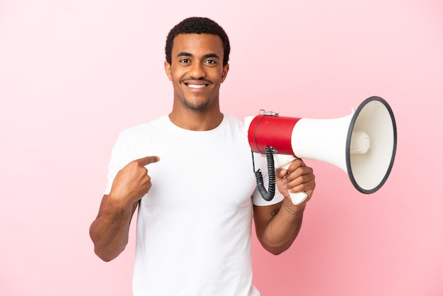 Afro-amerikaanse knappe man op geïsoleerde roze achtergrond met een megafoon en met verrassende gezichtsuitdrukking