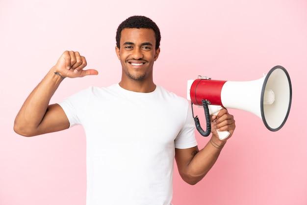 Afro-amerikaanse knappe man op geïsoleerde roze achtergrond met een megafoon en trots en zelfvoldaan