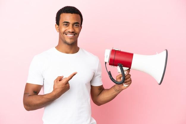 Afro-amerikaanse knappe man op geïsoleerde roze achtergrond met een megafoon en wijzende kant