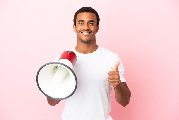 Afro-amerikaanse knappe man op geïsoleerde roze achtergrond met een megafoon met duim omhoog