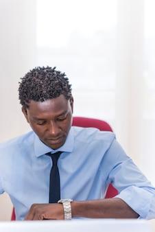 Afro-amerikaanse knappe zakenman die op zijn horloge naar de tijd kijkt