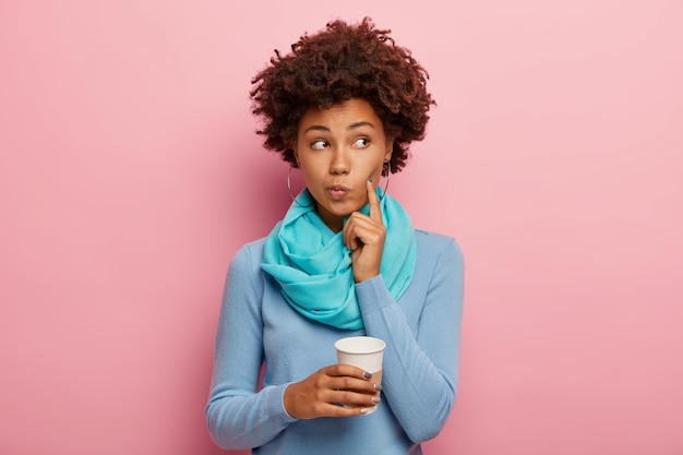 Afro-amerikaanse krullende vrouw houdt wijsvinger op wang, kijkt bedachtzaam opzij, overweegt iets met warme drank, houdt papieren beker vast, draagt blauwe trui, heeft koffiepauze geïsoleerd op roze muur