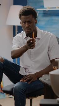Afro-amerikaanse kunstenaar die vaasontwerp bekijkt voor inspiratie om op canvas te tekenen in een creatieve studiokamer thuis. zwarte volwassen man die potlood gebruikt voor het tekenen van meesterwerken, het maken van beeldende kunst
