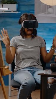 Afro-amerikaanse kunstenaar met vr-bril die technologie gebruikt om authentieke witte vaas te tekenen voor fine art-concept in studio. zwarte jonge vrouw met moderne hoofdtelefoonbril die wordt gebruikt om te tekenen