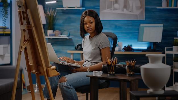 Afro-amerikaanse kunstenaar typen op laptopcomputer in studio