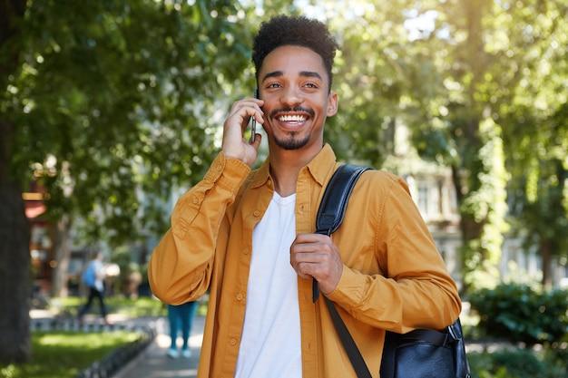 Afro-amerikaanse lachende man wandelen in het park, praten aan de telefoon met zijn vriendin, draagt in een geel shirt en een wit t-shirt met een rugzak op een schouder, glimlachend en geniet van de dag.