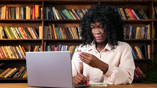Afro-amerikaanse leraar toont kaarten met letters op scherm