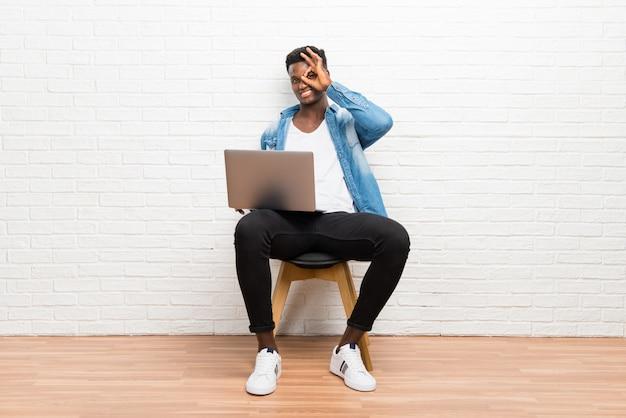 Afro-amerikaanse man aan het werk met zijn laptop maakt grappige en gekke gezicht emotie