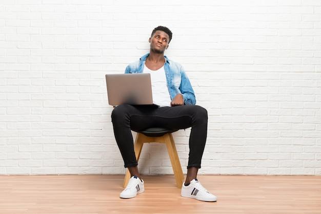 Afro-amerikaanse man aan het werk met zijn laptop twijfels en met verwarren gezichtsuitdrukking