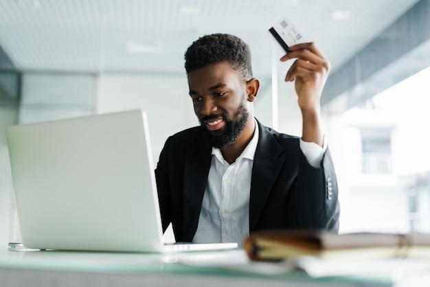 Afro-amerikaanse man betalen met creditcard online terwijl het doen van bestellingen via mobiel internet transactie met behulp van mobiele bank applicatie.