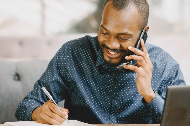 Afro-amerikaanse man die achter een laptop werkt en aan de telefoon praat