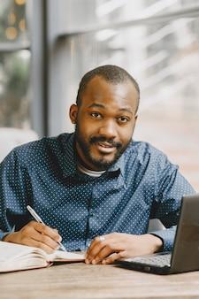 Afro-amerikaanse man die achter een laptop werkt en in een notitieblok schrijft. man met baard zit in een café.