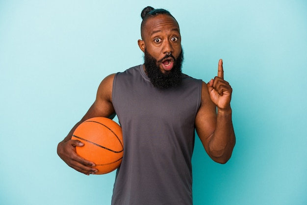 Afro-amerikaanse man die basketbal speelt geïsoleerd op blauwe achtergrond met een geweldig idee, concept van creativiteit.