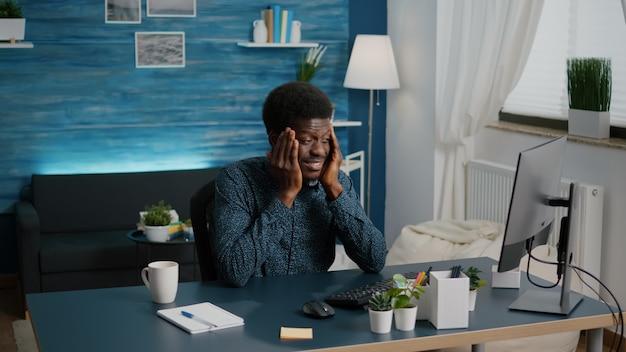 Afro-amerikaanse man die benadrukt dat hij grote hoofdpijn heeft