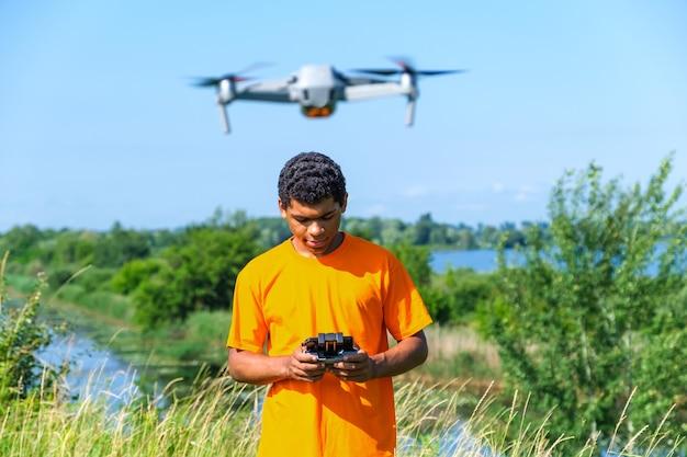Afro-amerikaanse man die drone met controller in handen op de weide bedient