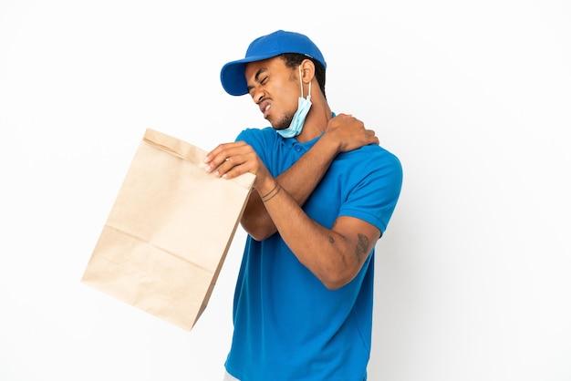 Afro-amerikaanse man die een zak afhaalmaaltijden neemt geïsoleerd op een witte achtergrond die lijdt aan pijn in de schouder omdat hij moeite heeft gedaan