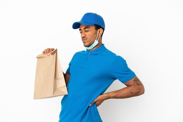Afro-amerikaanse man die een zak afhaalmaaltijden neemt geïsoleerd op een witte achtergrond die lijdt aan rugpijn omdat hij zich heeft ingespannen