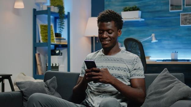 Afro-amerikaanse man die lacht en smartphone gebruikt