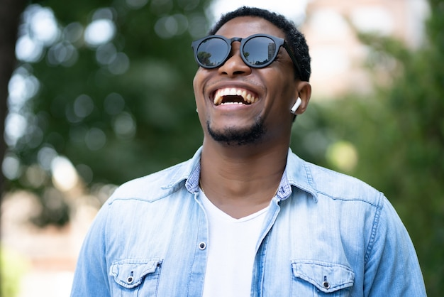 Afro-amerikaanse man die lacht terwijl hij buiten op straat staat