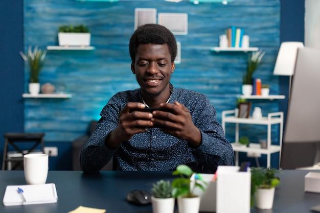 Afro-amerikaanse man die lacht terwijl hij een smartphone aan het bureau gebruikt om sociale media op afstand te controleren g ...