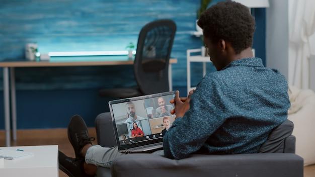 Afro-amerikaanse man die laptop gebruikt voor online internetconferentiechat met zijn collega's op afstand werken...