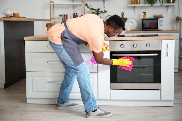Afro-amerikaanse man die oven in keuken schoonmaakt